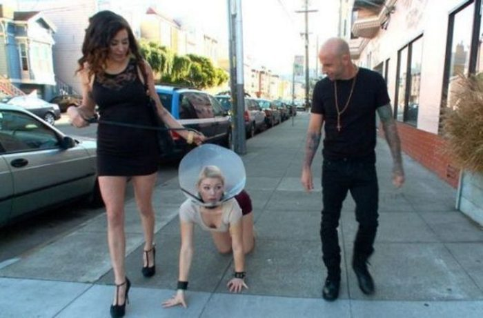 девушка ползет на коленях на поводке по улице