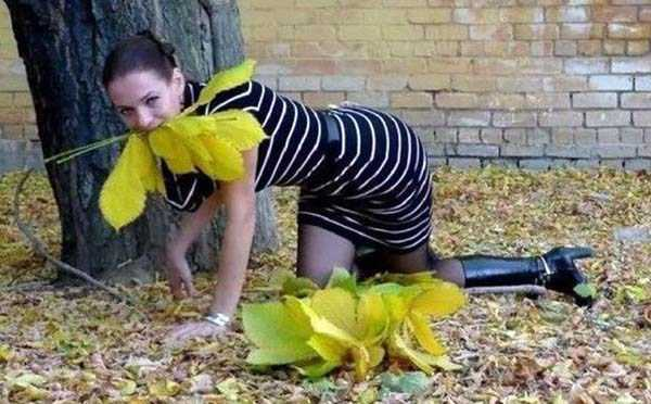 девушка на коленях с листьями во рту