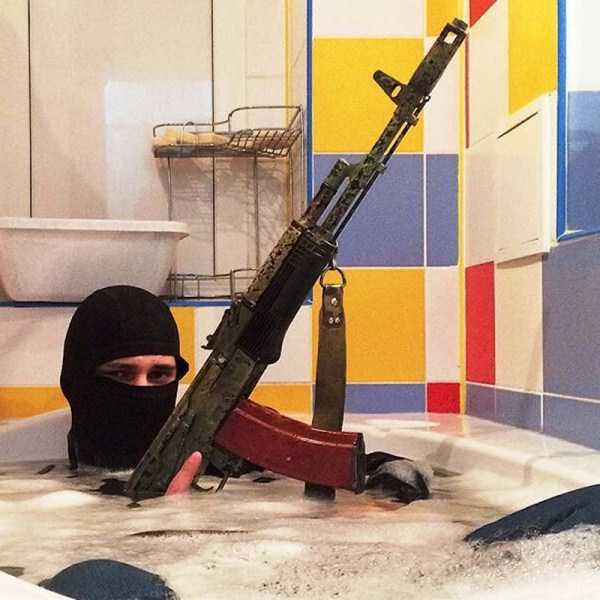 парень в балаклаве с оружием в ванне