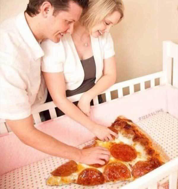 родители возле кроватки с пиццей