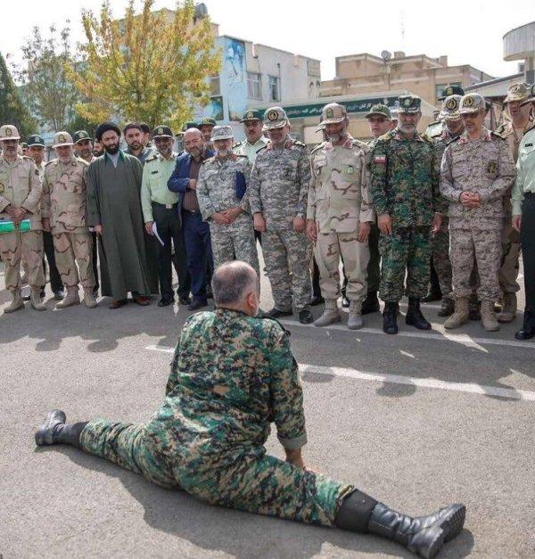 солдат сидит на шпагате перед ротой