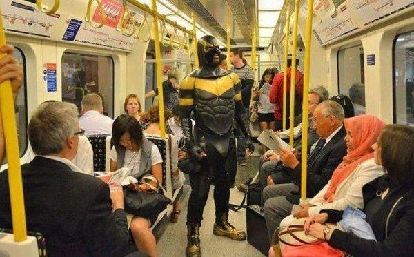 человек в костюме супергероя в метро