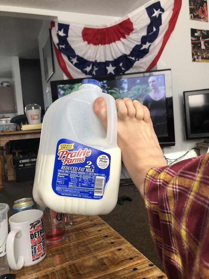 галлон с молоком на ноге
