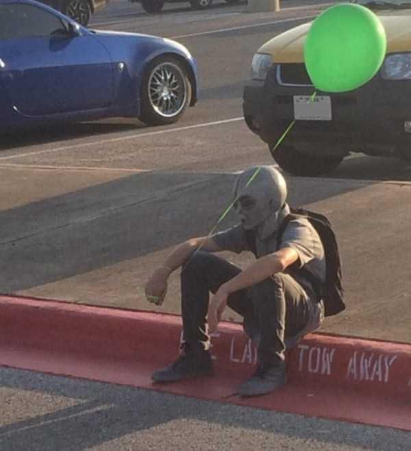 парень с зеленым шаром сидит на бордюре
