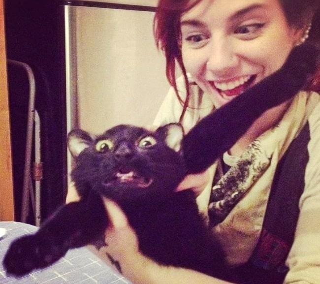 девушка держит черного кота