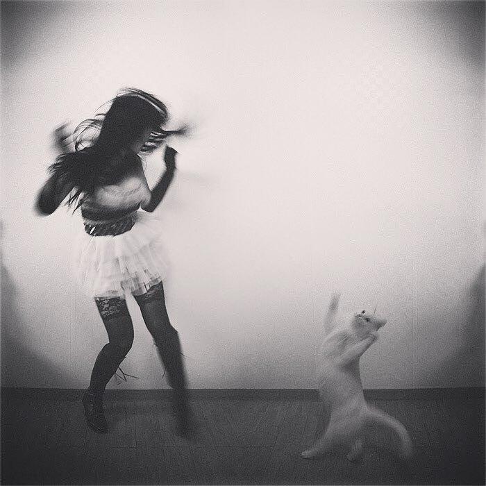 девушка танцует с белой кошкой
