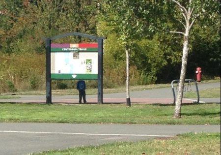 мальчик спрятался за рекламным щитом