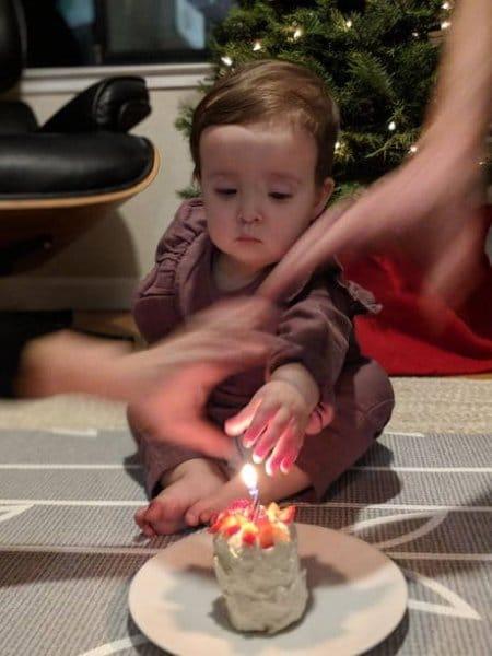 девочка тянется пальцем к свече на торте