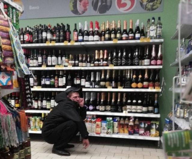 парень в алкогольном отделе в супермаркете