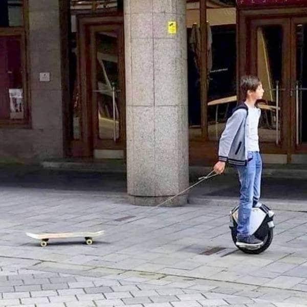 мальчик везет за собой скейт