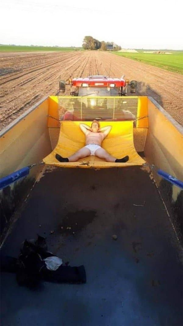 мужчина спит в гамаке в кузове трактора