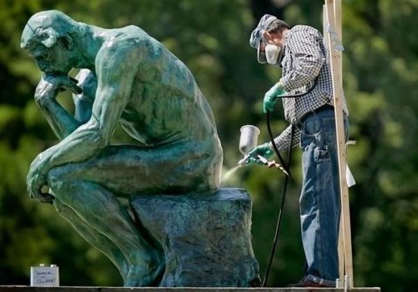 мужчина моет статую