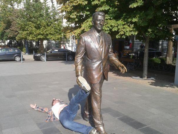 парень лежит рядом со статуей