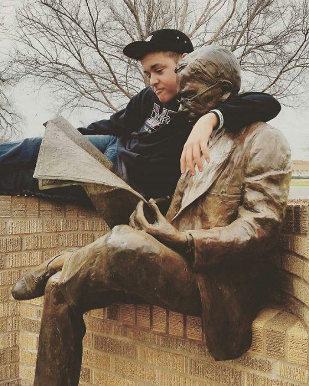 парень в обнимку с памятником