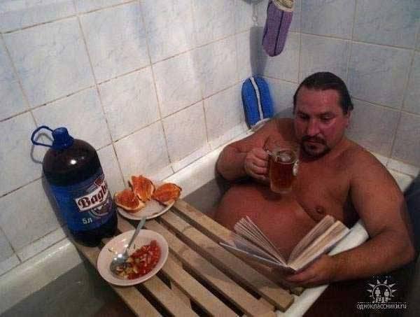 мужчина читает и ест в ванне