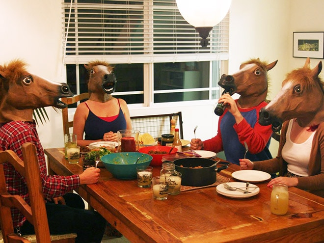 люди за столом в масках лошади