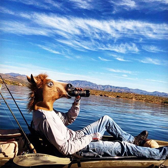 парень пьет пиво в лошадиной маске
