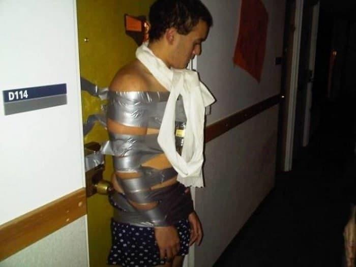 парень привязан изолентой к двери