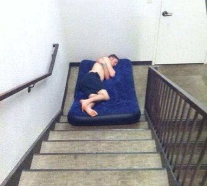парень спит на матрасе на лестнице