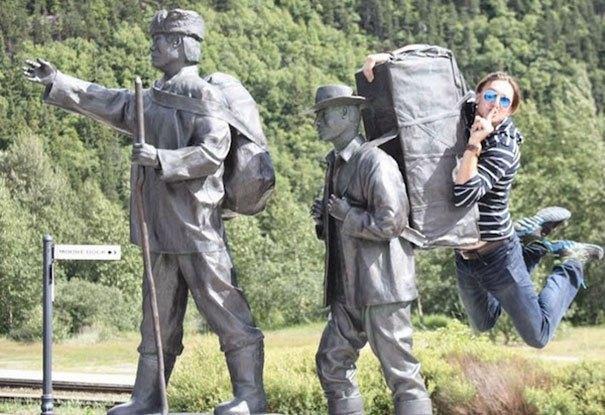 парень висит на памятнике