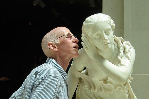 пожилой мужчина рядом со скульптурой