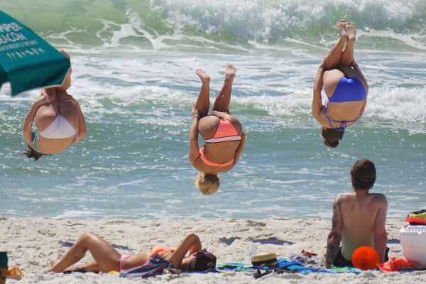 девушки делают сальто назад на пляже