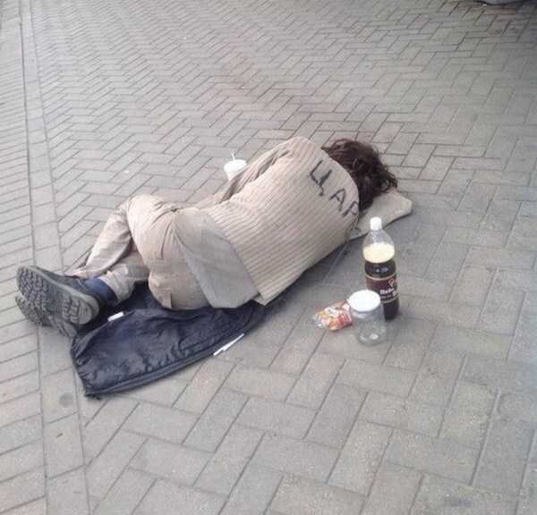 мужчина спит на асфальте