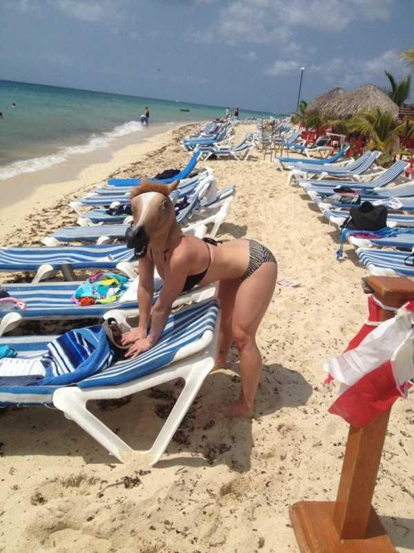 женщина в маске лошади на пляже