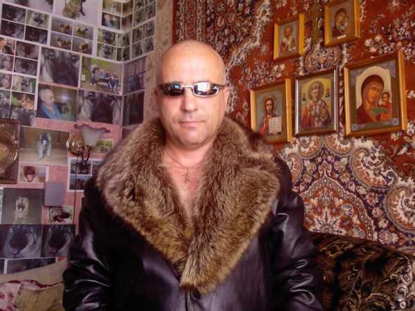 мужчина в меховой куртке на фоне ковра
