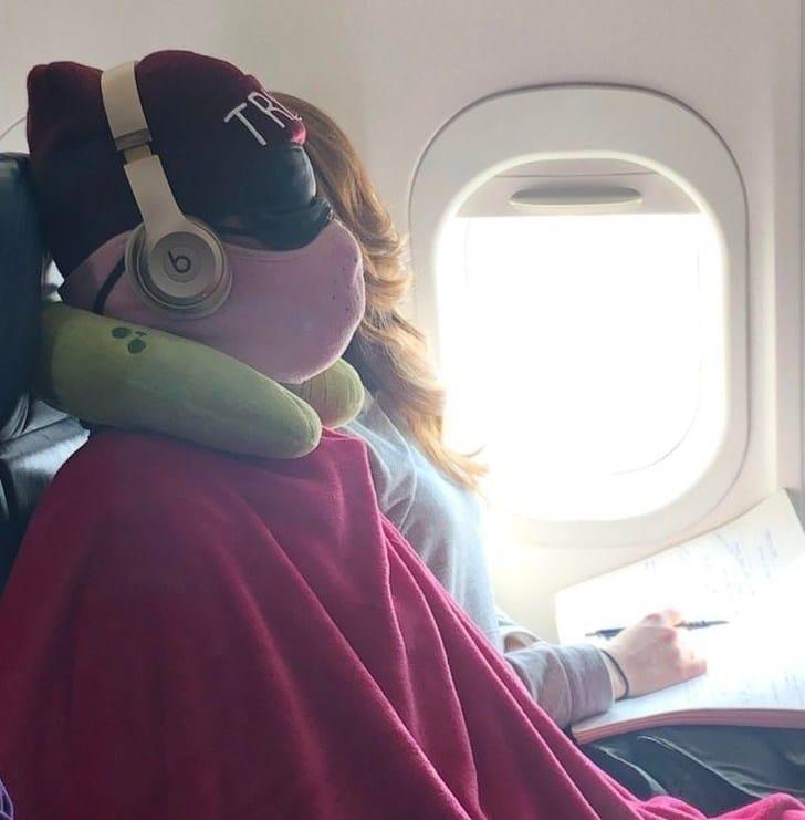 парень в маске и наушниках в самолете