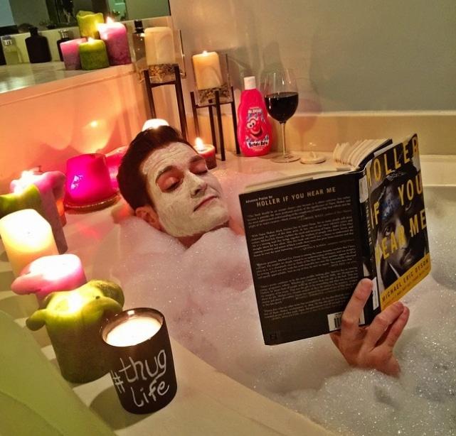 парень принимает пенную ванну с книгой