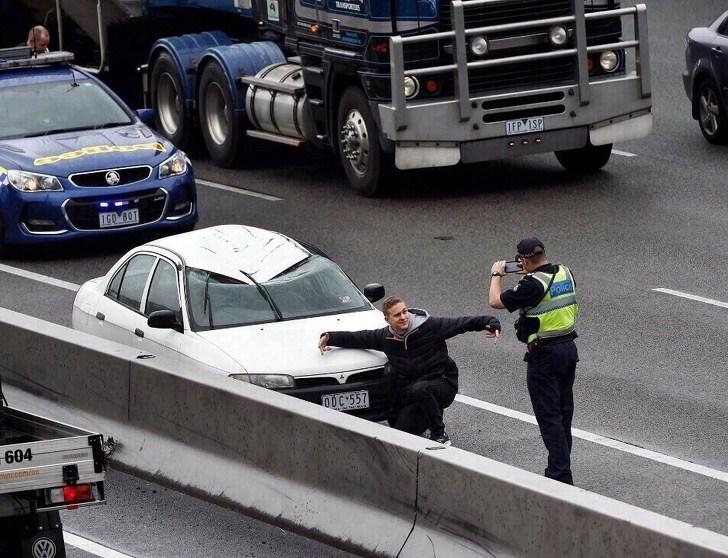 парень фотографируется на фоне разбитой машины