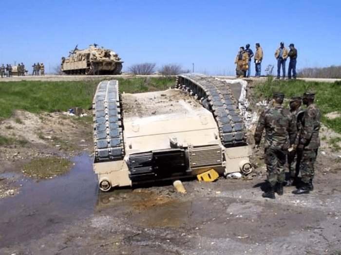 солдаты рядом с перевернутым танком