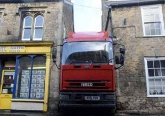 грузовик застрял между домами