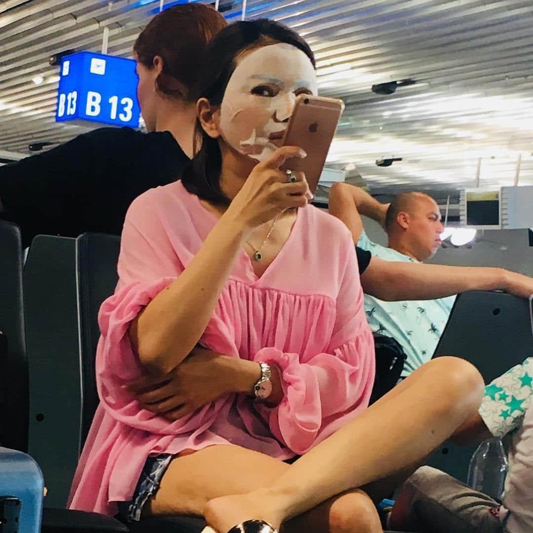 девушка в тканевой маске с телефоном