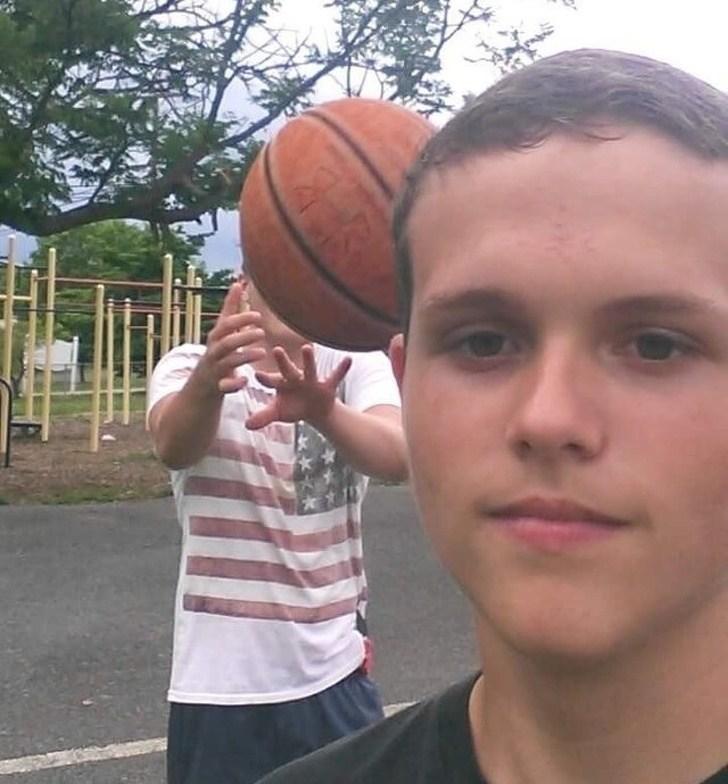 мальчик с баскетбольным мячом за головой