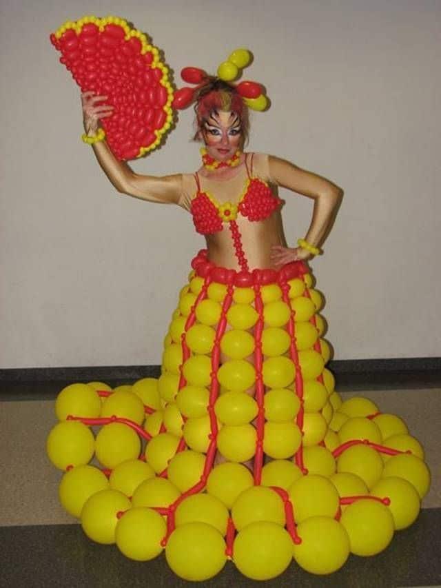 женщина в желтом платье из шариков