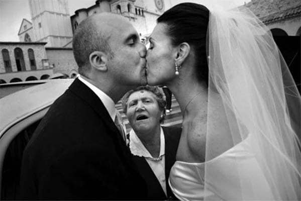мужчина смотрит на целующихся молодоженов