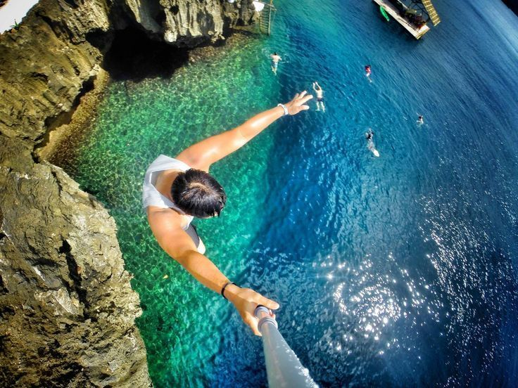 парень прыгает в воду с обрыва