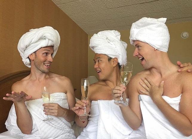 парни с полотенцами на голове пьют шампанское