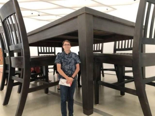 парень на фоне огромного стола