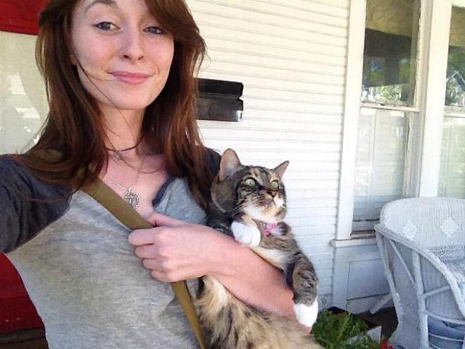 девушка держит испуганного кота
