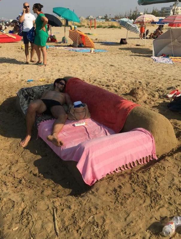 парень спит на диване из песка