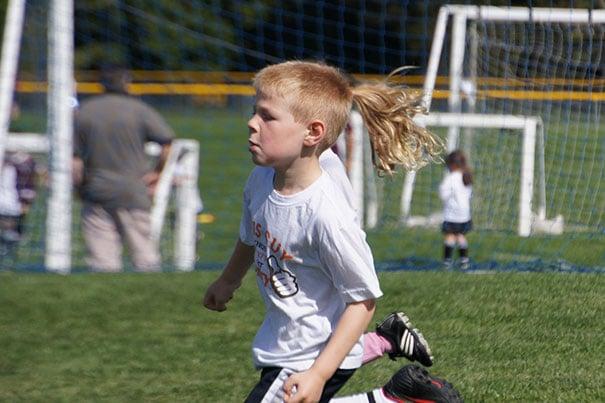 мальчик бежит по футбольному полю