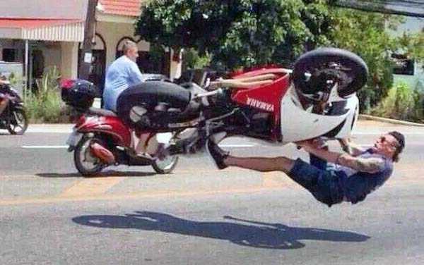 мужчина падает с мотоцикла