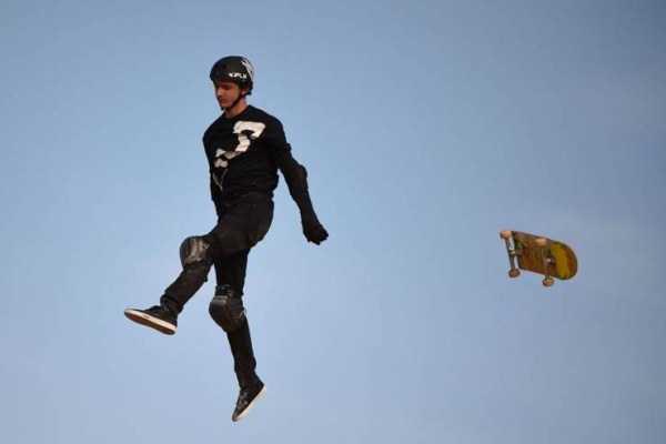 мужчина и скейтборд в воздухе