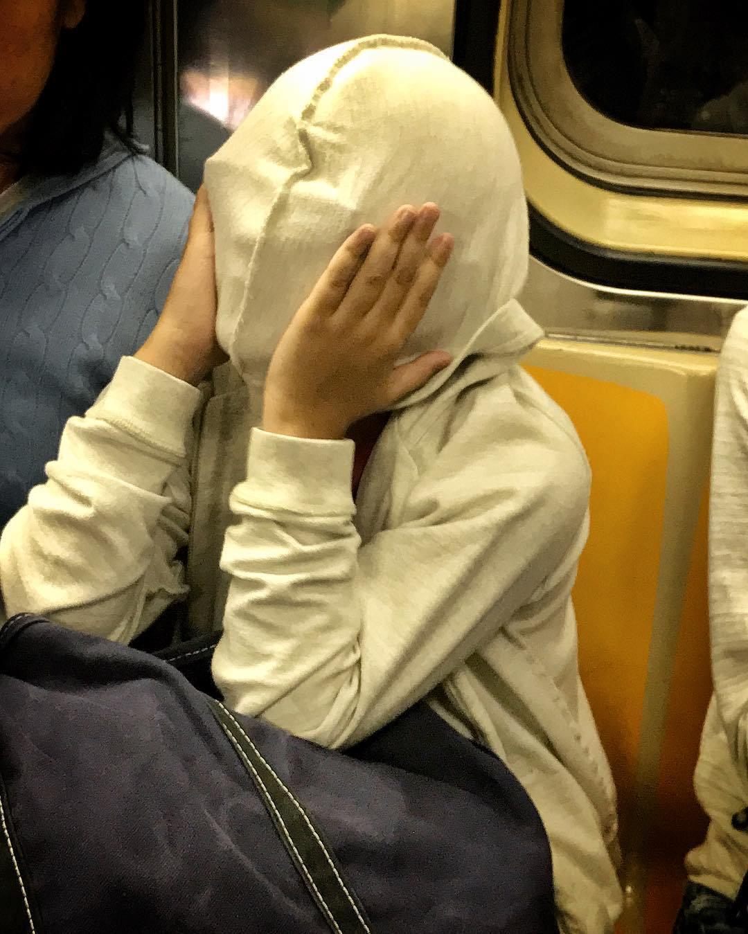 девушка с капюшоном на лице в метро