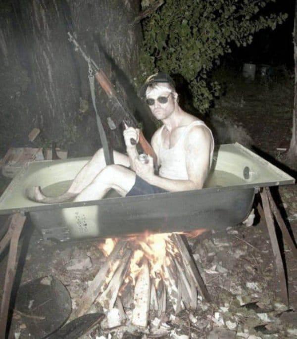 парень сидит в ванне над огнем
