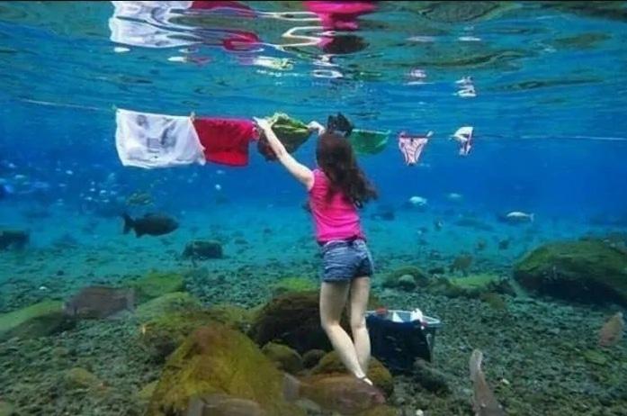 девушка развешивает белье под водой