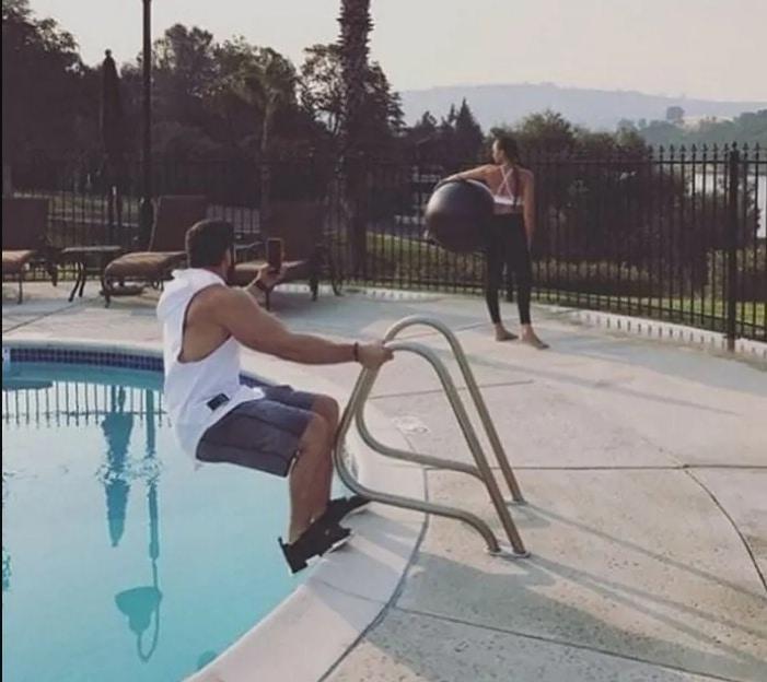 парень фотографирует девушку у бассейна